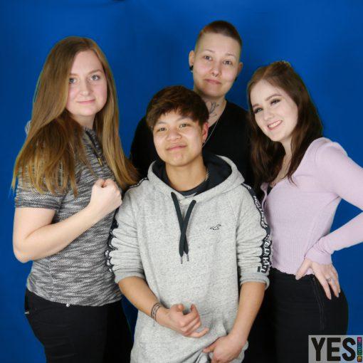 Die vier Hauptmitglieder im Vordergrund Hintergrund dunkel blau